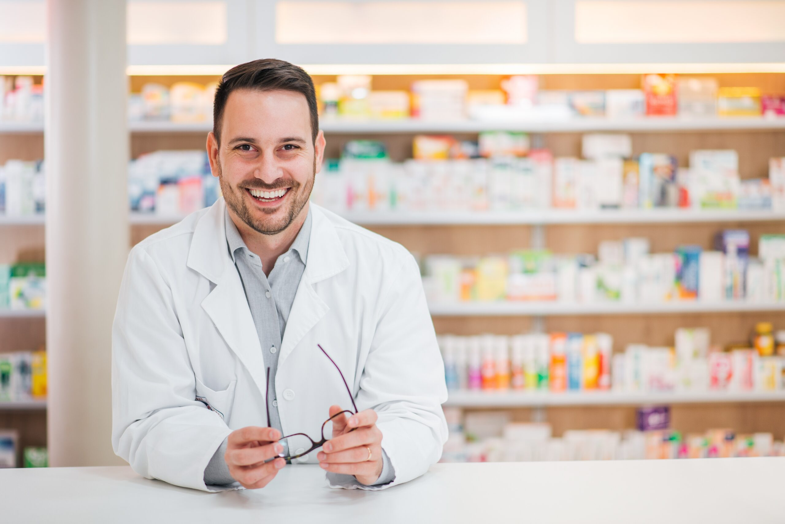 Portrait of a cheerful handsome pharmacist leaning on counter at drugstore.